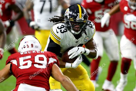 Stock Photo of Pittsburgh Steelers running back Trey Edmunds (33) runs as Arizona Cardinals linebacker Joe Walker (59) defends during the first half of an NFL football game, in Glendale, Ariz