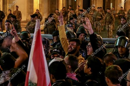 Protesters carry placards and wave Lebanese flags as they shout slogans against the parlianment members, during an anti-government protest in front of the Parliament building in Beirut, Lebanon, 08 December 2019. Protests in Lebanon are continuing since it first erupted on 17 October, as protesters aim to apply pressure on the country's political leaders to over what they view as a lack of progress following the prime minister's resignation on 29 October,  demand to speed up the process to appointment of a new prime minister, without the corrupt political class. Lebanese President Michel Aoun called for formal consultations on 09 December with lawmakers to designate a new prime minister, but it was canceled after the candidate Samir Khatib announced his withdrawal from the candidacy, after his visit Dar Al Fatwa, as said to media that, the country's top Sunni religious authority told him the community supports resigned prime minister Saad Hariri to take back the post.
