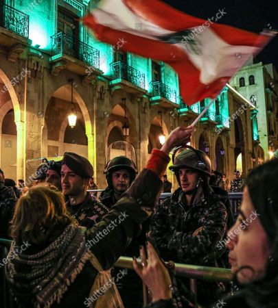 A protester waves the Lebanese flags in front of Lebanese policemen at a barricade, during an anti-government protest in front of the Parliament building in Beirut, Lebanon, 08 December 2019. Protests in Lebanon are continuing since it first erupted on 17 October, as protesters aim to apply pressure on the country's political leaders to over what they view as a lack of progress following the prime minister's resignation on 29 October,  demand to speed up the process to appointment of a new prime minister, without the corrupt political class. Lebanese President Michel Aoun called for formal consultations on 09 December with lawmakers to designate a new prime minister, but it was canceled after the candidate Samir Khatib announced his withdrawal from the candidacy, after his visit Dar Al Fatwa, as said to media that, the country's top Sunni religious authority told him the community supports resigned prime minister Saad Hariri to take back the post.