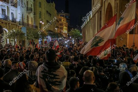 Stock Picture of Protesters carry placards and wave Lebanese flags as they shout slogans against the parlianment members, during an anti-government protest in front of the Parliament building in Beirut, Lebanon, 08 December 2019. Protests in Lebanon are continuing since it first erupted on 17 October, as protesters aim to apply pressure on the country's political leaders to over what they view as a lack of progress following the prime minister's resignation on 29 October,  demand to speed up the process to appointment of a new prime minister, without the corrupt political class. Lebanese President Michel Aoun called for formal consultations on 09 December with lawmakers to designate a new prime minister, but it was canceled after the candidate Samir Khatib announced his withdrawal from the candidacy, after his visit Dar Al Fatwa, as said to media that, the country's top Sunni religious authority told him the community supports resigned prime minister Saad Hariri to take back the post.