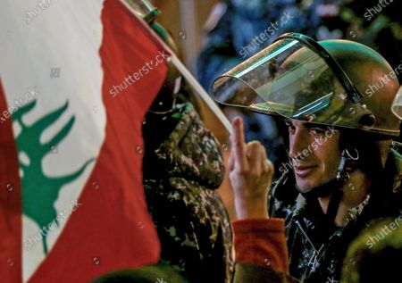 Stock Photo of A protester waves the Lebanese flags in front of Lebanese policemen at a barricade, during an anti-government protest in front of the Parliament building in Beirut, Lebanon, 08 December 2019. Protests in Lebanon are continuing since it first erupted on 17 October, as protesters aim to apply pressure on the country's political leaders to over what they view as a lack of progress following the prime minister's resignation on 29 October,  demand to speed up the process to appointment of a new prime minister, without the corrupt political class. Lebanese President Michel Aoun called for formal consultations on 09 December with lawmakers to designate a new prime minister, but it was canceled after the candidate Samir Khatib announced his withdrawal from the candidacy, after his visit Dar Al Fatwa, as said to media that, the country's top Sunni religious authority told him the community supports resigned prime minister Saad Hariri to take back the post.