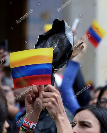 A woman bangs on a pot during a musical protest against the government of President Ivan Duque in Bogota, Colombia, . The performances coincide with recent demonstrations calling on Duque to throw out a proposed tax reform, improve conditions for threatened social leaders and fully implement Colombia's historic peace accord with leftist rebels