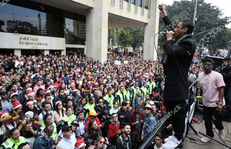 Colombian rappers Juan Pablo Barragan and Yoky Barrios, in pink shirt, perform during a musical protest against the government of President Ivan Duque in Bogota, Colombia, . The performances coincide with recent demonstrations calling on Duque to throw out a proposed tax reform, improve conditions for threatened social leaders and fully implement Colombia's historic peace accord with leftist rebels