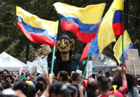 A giant puppet towers over anti-government protesters gathering for a musical protest against the government of President Ivan Duque in Bogota, Colombia, . The performances coincide with recent demonstrations calling on Duque to throw out a proposed tax reform, improve conditions for threatened social leaders and fully implement Colombia's historic peace accord with leftist rebels