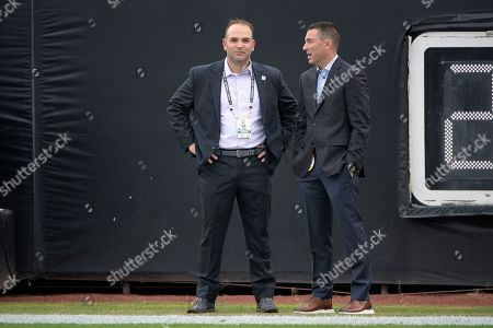 Jacksonville Jaguars general manager David Caldwell, left, talks with Los Angeles Chargers general manager Tom Telesco on the field before an NFL football game, in Jacksonville, Fla