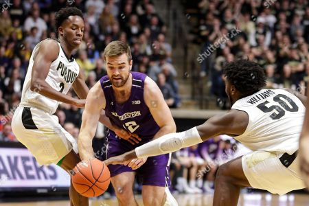 Trevion Williams, Eric Hunter Jr., \n13#3. Northwestern guard Pat Spencer (12) drives between Purdue guard Eric Hunter Jr. (2) and forward Trevion Williams (50) during the first half of an NCAA college basketball game in West Lafayette, Ind