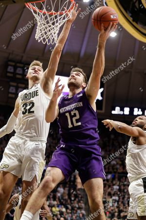 Northwestern guard Pat Spencer (12) shoots between Purdue center Matt Haarms (32) and guard Jahaad Proctor (3) during the first half of an NCAA college basketball game in West Lafayette, Ind