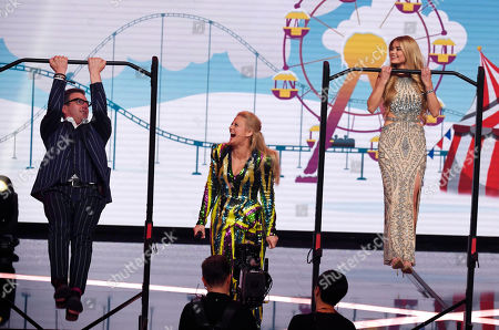 "Stock Photo of German influencer Pamela Reif makes pull ups together with actor Hans Sign, left, as presenter Barbara Schoeneberger, center, looks on during the charity gala ""Ein Herz fuer Kinder"" (a heart for children) in Berlin, Germany"