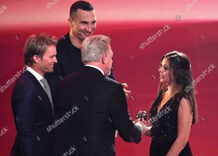 """Former F1 driver Nico Rosberg, left,tennis legend Boris Becker, center, and boxer Wladimir Klitschko give the honorary heart award to Lena Palm, right, during the charity gala """"Ein Herz fuer Kinder"""" (a heart for children) in Berlin, Germany"""