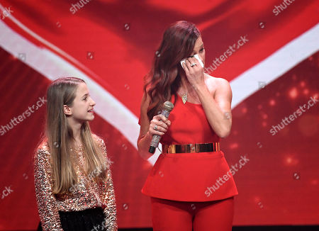 "Singer Andrea Berg, right, wipes her face during the charity gala ""Ein Herz fuer Kinder"" (a heart for children) in Berlin, Germany"