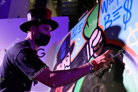 Alec Monopoly painting a mural for the auction