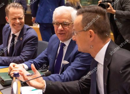 Polish Foreign Minister Jacek Czaputowicz, center, speaks with Hungarian Foreign Minister Peter Szijjarto, right, during a meeting of EU foreign ministers at the Europa building in Brussels, . European Union foreign ministers are debating how to respond to a controversial deal between Turkey and Libya that could give Ankara access to a contested economic zone across the Mediterranean Sea