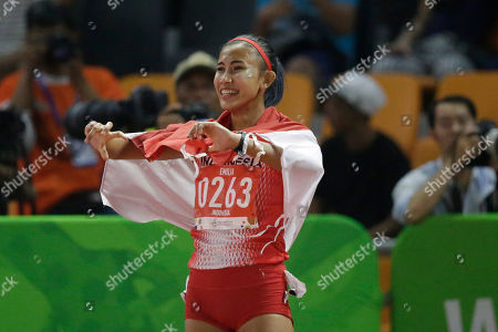 Stock Picture of Indonesia's Emilia Nova celebrates with her national flag after winning in the women's 100m hurdles final during the athletics competition at the 30th Southeast Asian Games at Athletics Stadium in New Clark City, Tarlac province, northern Philippines on