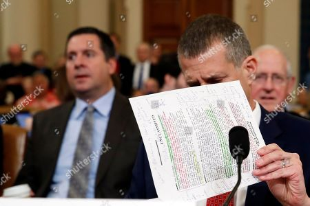 Republican staff attorney Steve Castor reviews notes as Rep. Devin Nunes, R-Calif., left, watches as the House Judiciary Committee prepares to hear investigative findings in the impeachment inquiry of President Donald Trump, on Capitol Hill in Washington