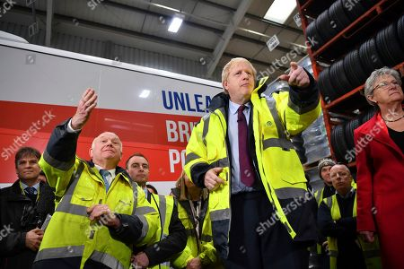 Stock Photo of Britain's Prime Minister Boris Johnson talks during a question and answer session, part of a General Election campaign visit to Ferguson's Transport in Washington, England, . CEO Alan Ferguson stands at left. Britain goes to the polls on Dec. 12