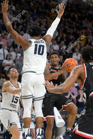 New Williams, Abel Porter, Alphonso Anderson. Fresno State guard New Williams takes a shot as Utah State guard Abel Porter (15) and forward Alphonso Anderson (10) defend during the second half of an NCAA college basketball game, in Logan, Utah