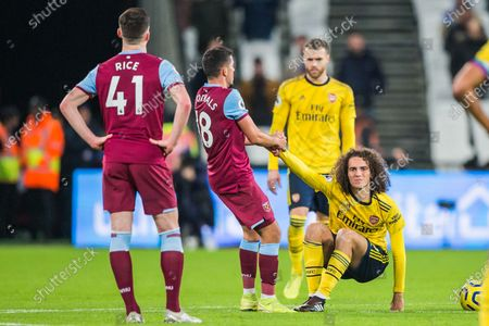 Matteo Guendouzi (Arsenal) on the ground and Pablo Fornals (West Ham) comes straight over to get him on his feet keen to get play underway again during the Premier League match between West Ham United and Arsenal at the London Stadium, London