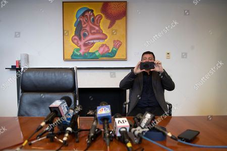 """Artist David Datuna takes a photo of reporters during a news conference, in New York. Datuna ate """"Comedian,"""" a spotty banana duct-taped to a wall by artist Maurizio Cattelan, at Art Basel Miami Saturday"""