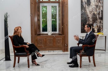 """In this photo released on by the Syrian official news agency SANA, Syrian President Bashar Assad, right, speaks during an interview with Monica Maggioni, left, the CEO of Italy's Rai News 24, in Damascus, Syria. Assad said in an interview aired Monday that the global chemical weapons watchdog has faked and falsified a report over an attack near the capital Damascus last year """"just because the Americans wanted them to do so"""