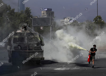 An anti-government demonstrator sprays fire extinguisher towards a Chile's police water cannon during a protest in Santiago, Chile, . Student protests have become a nationwide call for socio-economic equality and better social services, so far forcing Chilean President Sebastian Pinera to increase benefits for the poor and disadvantaged and start a process of constitutional reform