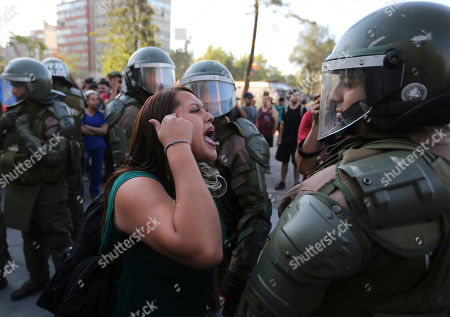 A demonstrator argues with an anti riot police officer during a protest in Santiago, Chile, . Student protests have become a nationwide call for socio-economic equality and better social services, so far forcing Chilean President Sebastian Pinera to increase benefits for the poor and disadvantaged and start a process of constitutional reform