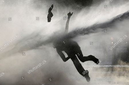 Stock Photo of An anti-government demonstrator is sprayed by a police water cannon during a protest in Santiago, Chile, . Student protests have become a nationwide call for socio-economic equality and better social services, so far forcing Chilean President Sebastian Pinera to increase benefits for the poor and disadvantaged and start a process of constitutional reform