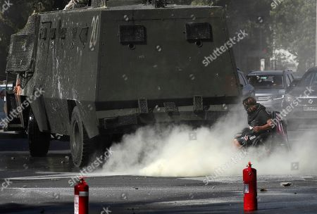 Stock Image of An anti-government demonstrator on a wheel chair sprays fire extinguisher towards a Chile's police water cannon during a protest in Santiago, Chile, . Student protests have become a nationwide call for socio-economic equality and better social services, so far forcing Chilean President Sebastian Pinera to increase benefits for the poor and disadvantaged and start a process of constitutional reform