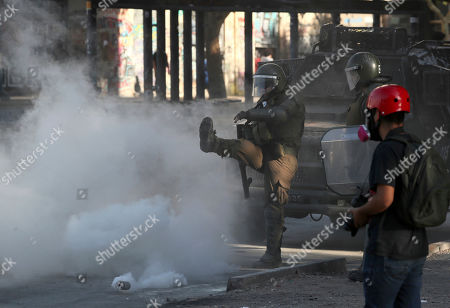 A police officer kicks back a tear gas canister toward demonstrators during a protest in Santiago, Chile, . Student protests have become a nationwide call for socio-economic equality and better social services, so far forcing Chilean President Sebastian Pinera to increase benefits for the poor and disadvantaged and start a process of constitutional reform