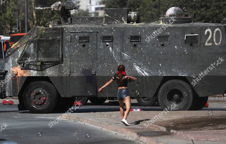 An anti-government protester throws a stone at a Chile's police water cannon during a protest in Santiago, Chile, . Student protests have become a nationwide call for socio-economic equality and better social services, so far forcing Chilean President Sebastian Pinera to increase benefits for the poor and disadvantaged and start a process of constitutional reform