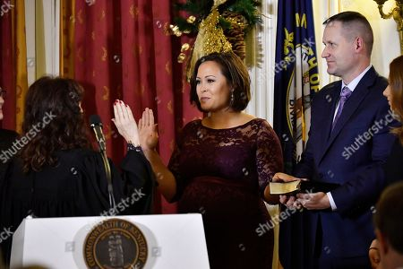Jacqueline Coleman raises her hand as her husband, Jack Coleman, holds the Bible while Kentucky Supreme Court Justice Michelle M. Keller, left, gives the oath of office to Coleman to become lieutenant governor, in Frankfort, Ky., early
