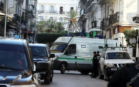 Members of Algeria's Research and Intervention Brigades (BRI) stand guard next to a vehicle carrying two former prime ministers, in Algiers, Algeria, 10 December 2019. The two former Prime Ministers Abdelmalek Sellal and Ahmed Ouyahia are currently under trial on charges of money laundering and corruption.