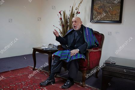 Former Afghan President Hamid Karzai gestures while speaking during an interview with The Associated Press, in Kabul, Afghanistan, . Karzai, whose final years in power were characterized by a cantankerous relationship with the United States, said on Tuesday that Washington used blackmail and corruption to manipulate his officials, undermine his government and foment violence among the country's many factions