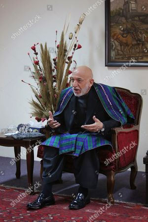 Former Afghan President Hamid Karzai speaks during an interview with The Associated Press, in Kabul, Afghanistan, . Karzai, whose final years in power were characterized by a cantankerous relationship with the United States, said on Tuesday that Washington used blackmail and corruption to manipulate his officials, undermine his government and foment violence among the country's many factions