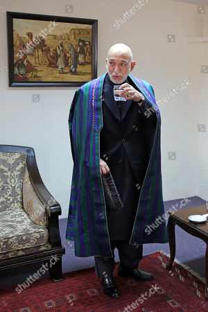 Former Afghan President Hamid Karzai drinks a glass of water after an interview with The Associated Press, in Kabul, Afghanistan, . Karzai, whose final years in power were characterized by a cantankerous relationship with the United States, said on Tuesday that Washington used blackmail and corruption to manipulate his officials, undermine his government and foment violence among the country's many factions