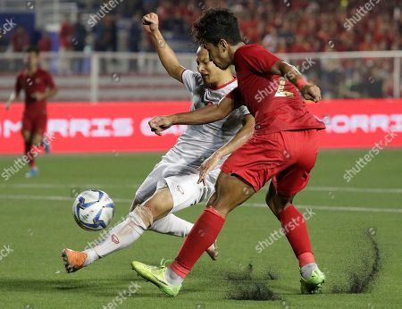 Vietnam's Trong Hoang Nguyen, left, tries to control the ball against Indonesia's Ardiles Osvaldo Haay during the men's football finals match at the 30th South East Asian Games in Manila, Philippines on . Vietnam won gold
