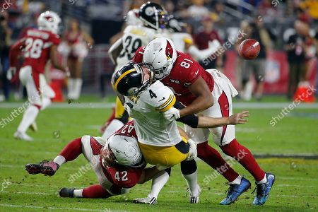 Pittsburgh Steelers punter Jordan Berry (4) is hit by Arizona Cardinals tight end Darrell Daniels (81) and linebacker Dennis Gardeck (42) on a fake punt attempt during the second half of an NFL football game, in Glendale, Ariz. The Cardinals took over on downs