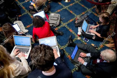 Reporters sit on the floor in a crowded room where House Speaker Nancy Pelosi of Calif., Chairwoman of the House Financial Services Committee Maxine Waters, D-Calif., Chairman of the House Judiciary Committee Jerrold Nadler, D-N.Y., Chairwoman of the House Oversight and Reform Committee Carolyn Maloney, D-N.Y., Chairman of the House Ways and Means Committee Richard Neal, D-Mass., and Chairman of the House Intelligence Committee Adam Schiff, D-Calif., hold a news conference to unveil articles of impeachment against President Donald Trump, abuse of power and obstruction of Congress, on Capitol Hill in Washington