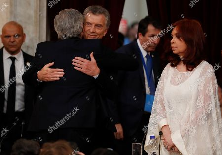 Outgoing president Mauricio Macri embraces new President Alberto Fernandez before presenting him the presidential sash as Vice President Cristina Fernandez de Kirchner looks on at the Congress in Buenos Aires, Argentina, . Fernandez became president of Argentina on Tuesday, returning the country's Peronist political movement to power amid an economic crisis and rising poverty