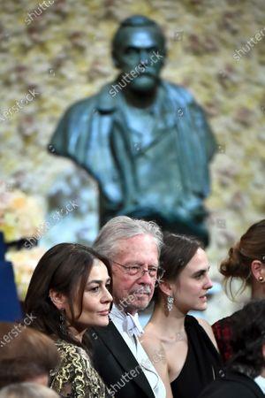 Austrian author Peter Handke (C), 2019 Nobel Prize for Literature laureate, and wife Sophie Semin Handke (L) stand in front of a bust of prize founder Alfred Nobel during the Nobel Prize award ceremony at Stockholm Concert Hall, in Stockholm, Sweden, 10 December 2019.
