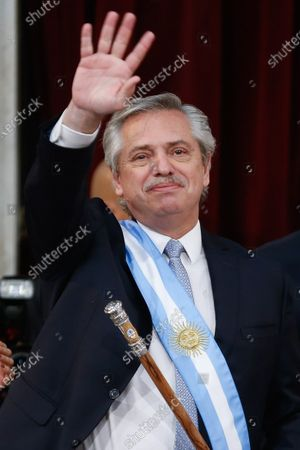 Argentinian President Alberto Fernandez waves upon receiving the baton from his predecessor Mauricio Macri (R), during the investiture ceremony at the Congress facilities in Buenos Aires, Argentina, 10 December 2019.