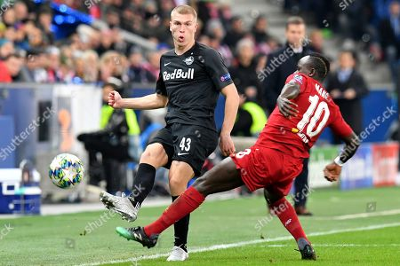 Salzburg's Rasmus Nissen Kristensen, left, is challenged by Liverpool's Sadio Mane during the group E Champions League soccer match between Salzburg and Liverpool, in Salzburg, Austria