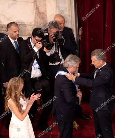 The new President of Argentina, Alberto Fernandez (C), receives the presidential band of the outgoing President, Mauricio Macri (R) during the inauguration in Buenos Aires, Argentina, 10 December 2019.