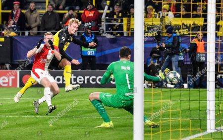 Dortmund's Julian Brandt, 2nd from left, scores his side's second goal against Slavia's goalkeeper Ondrej Kolar, right, during the Champions League Group F soccer match between Borussia Dortmund and Slavia Praha in Dortmund, Germany