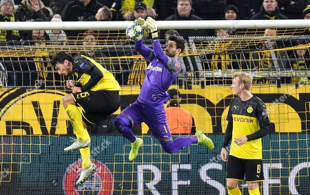 Dortmund's goalkeeper Roman Buerki jumps for the ball between Dortmund's Mats Hummels, left, and Dortmund's Julian Brandt, right, during the Champions League Group F soccer match between Borussia Dortmund and Slavia Praha in Dortmund, Germany