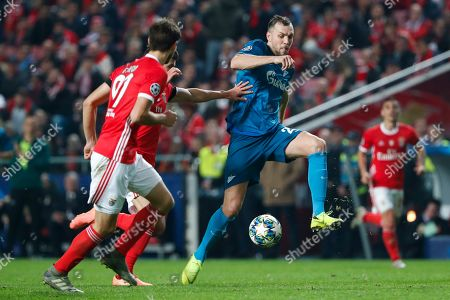 Zenit's Artem Dzyuba, right, battles for the ball with Benfica defenders during the Champions League group G soccer match between Benfica and Zenit St. Petersburg at the Luz stadium in Lisbon, . Benfica won 3-0