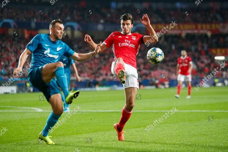 Benfica's Ruben Dias, right, vies for the ball with Zenit's Artem Dzyuba during the Champions League group G soccer match between Benfica and Zenit St. Petersburg at the Luz stadium in Lisbon