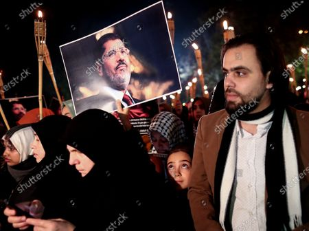 A little girl holds a picture of former Egyptian President Mohamed Morsi as protesters shout slogans against the Egyptian President Abdel Fattah al-Sisi during the protest for death penalty in Egypt, after the evening pray at Fatih Mosque in Istanbul, Turkey, 10 December 2019.