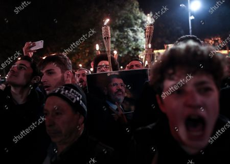 Protestors hold pictures of former Egyptian President Mohamed Morsi as they shout slogans against the Egyptian President Abdel Fattah al-Sisi during a protest for death penalty in Egypt, after the evening pray at Fatih Mosque in Istanbul, Turkey, 10 December 2019.