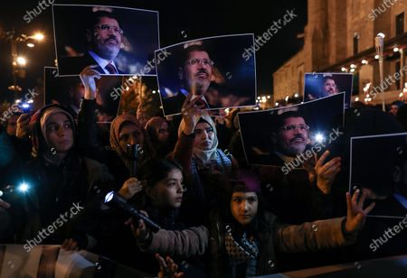 Stock Photo of Protestors hold picture of the former Egyptian President Mohamed Morsi during the protest for death penalty in Egypt, after the evening pray at Fatih Mosque in Istanbul, Turkey, 10 December 2019.