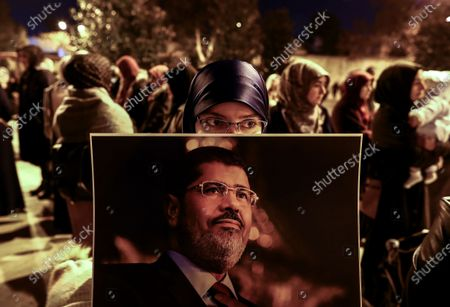 A woman holds a picture of former Egyptian President Mohamed Morsi during a protest for death penalty in Egypt, after the evening pray at Fatih Mosque in Istanbul, Turkey, 10 December 2019.